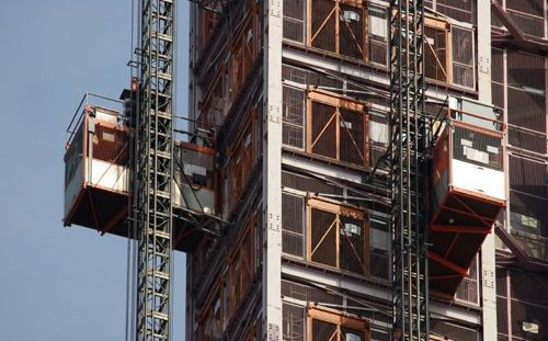 Hoist elevators that follow ANSI/ASSE A10.4-2016 on the side of a building in the process of being constructed