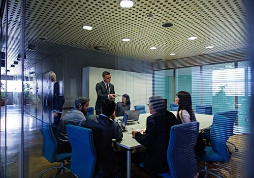 Man leading a meeting in an office and has the authority to from his Master Black Belt.