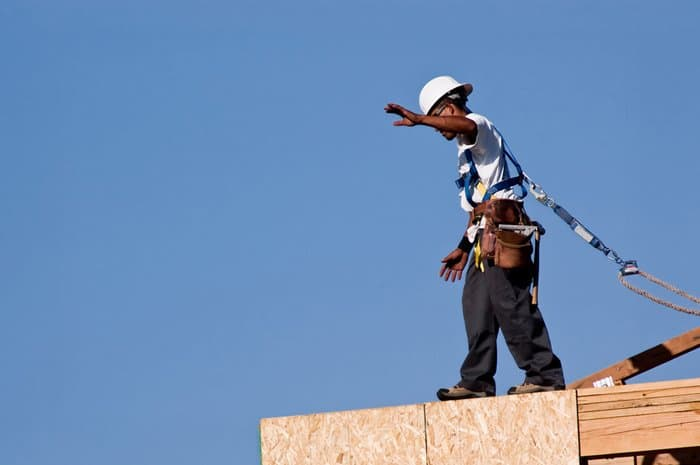 Construction worker who is protected by ANSI/ASSE Z359 and is standing on top of a building