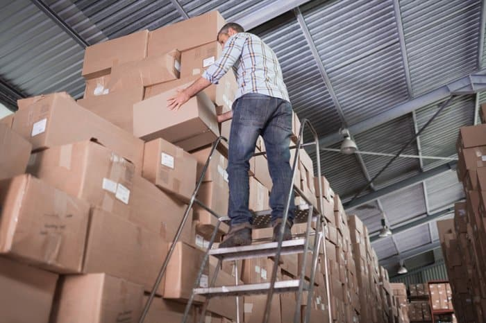 Depending on a stepstool to safely reach high boxes in industrial warehouse.