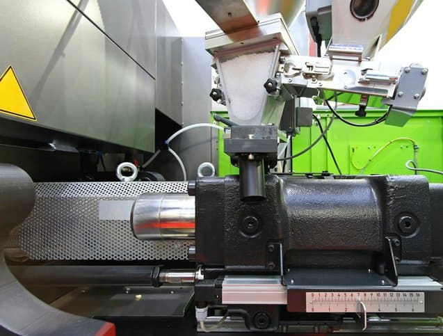 Close up of a green injection molding machine for plastic standards