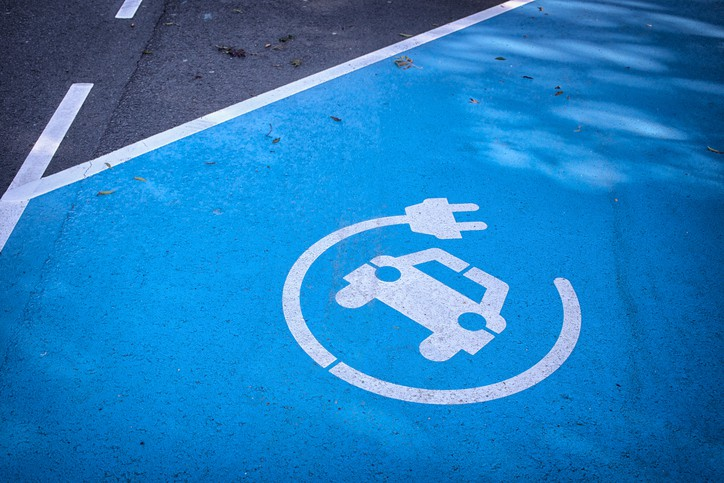 A blue parking space with a plug-in logo denoting where you can find an IEC 61851 EV charging station.