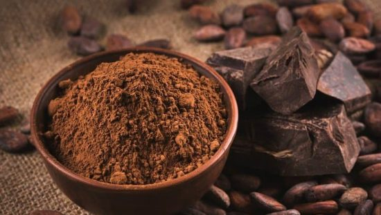 A bowl of cocoa powder next to pieces of chocolate and cocoa beans
