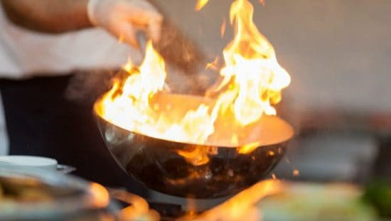 A kitchen fire burns bright without NFPA 96 and proper ventilation.