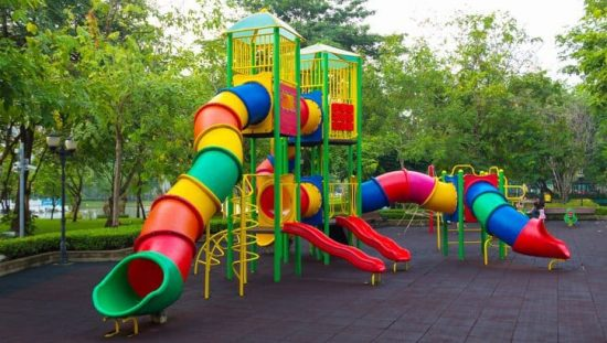 Colorful children's public playground kept safe with ASTM F1487-21.