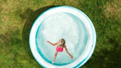 Young girl enjoying summer by leaping into a ASTM F2666-16 aboveground residential pool.