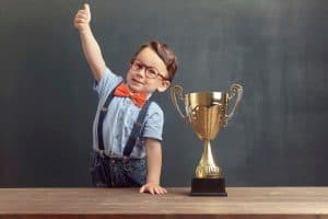 Young champion of the ANSI student paper competition wearing a bowtie and giving thumbs up.