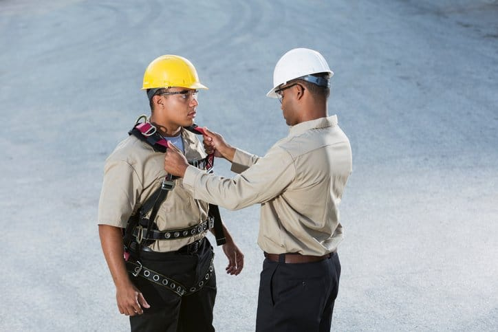 Supervisor preparing worker wearing hardhat for fall protection
