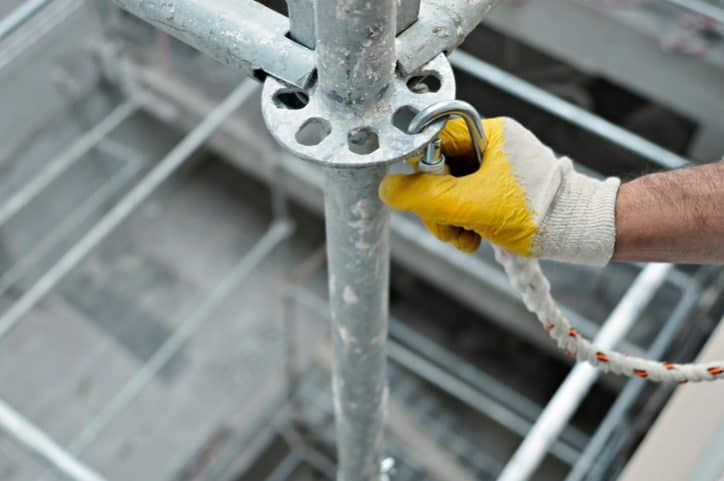 Worker locking in caribener to not violate fall protection OSHA requirements.