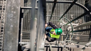 Man climbing a caged ladder while donning ANSI/ISEA 107-2020 High-Visibility Safety Apparel.
