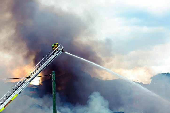 Firefighter on a ladder with water hose trying to control a fire by following NFPA Fire Code 1 2018