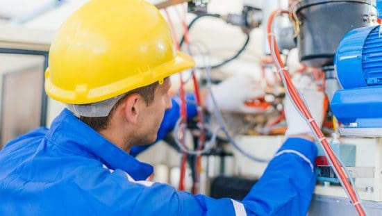 Worker repairing motor machinery and following NFPA 79-2018