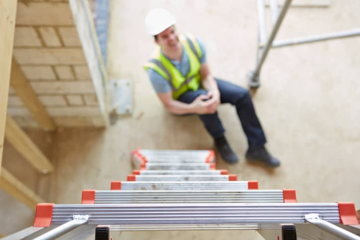 Man who aches in pain due to falling prey to overreaching, one of the common causes of ladder accidents