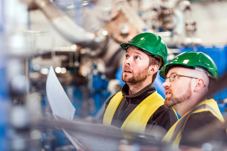 Two managers donning green hardhats conduct ISO 45001 continual improvement.