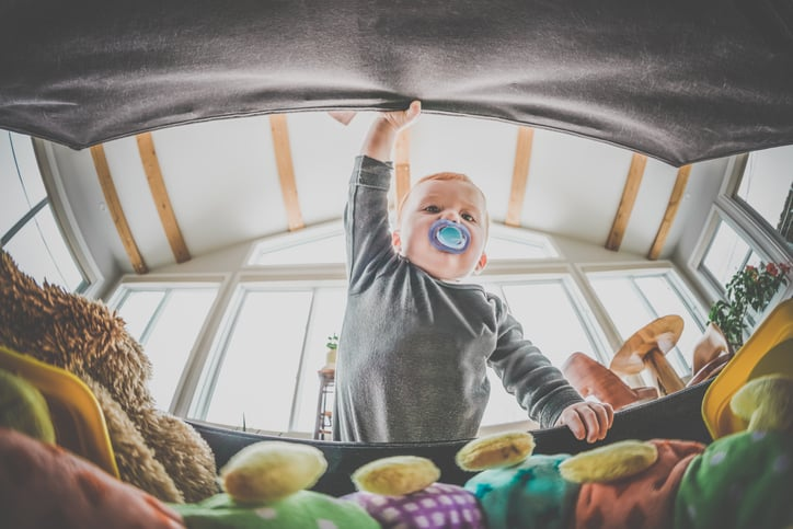 A baby opening a toy box filled with toys that follow ISO 8124 Standards