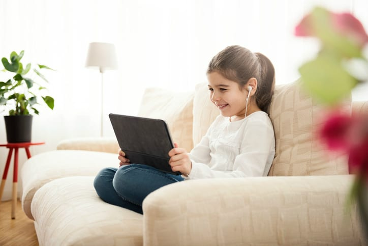 A child watching a video that follows ISO/IEC 14496 on a couch