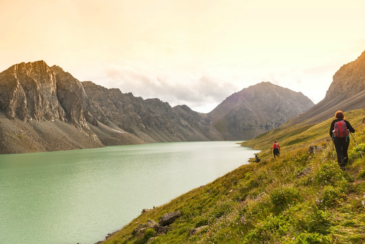 View of a lake within a valley and two hikers walk alongside it, which is symbolic of ISO 9004 2018