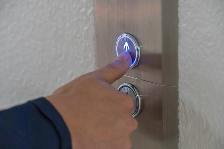 Pushing an elevator button up in accordance with ASME A17.1, or CSA B44, a binational standard.