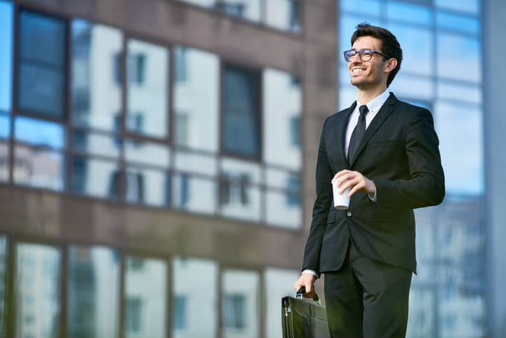 A man in a suit holding a coffee cup and a briefcase is smiling off into the distance which is symbolic for ISO 9004