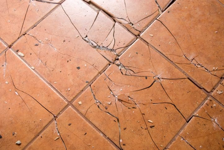 Tan ceramic tiles have been cracked and destroyed after an impact falling steel ball ASTM C1870 test.