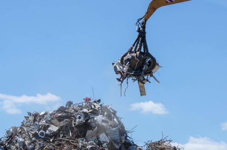 A yellow ASME B30.25-2018 Scrap and material handler in action picking up metal in scrapyard.