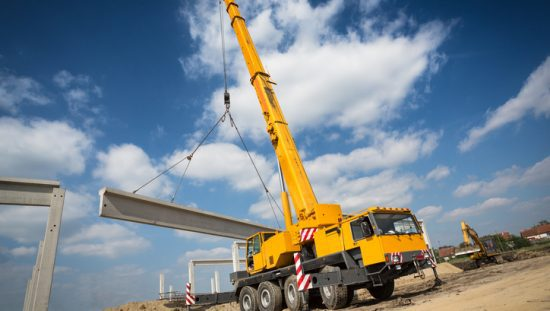Bright yellow ASME B30.5-2018 mobile crane lifting in action