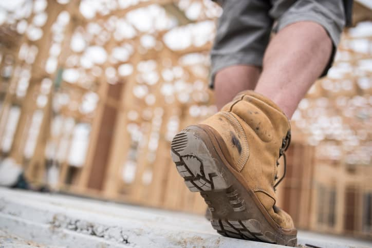 Man walking in protected construction site with brown ASTM F2412-18 tested boots.