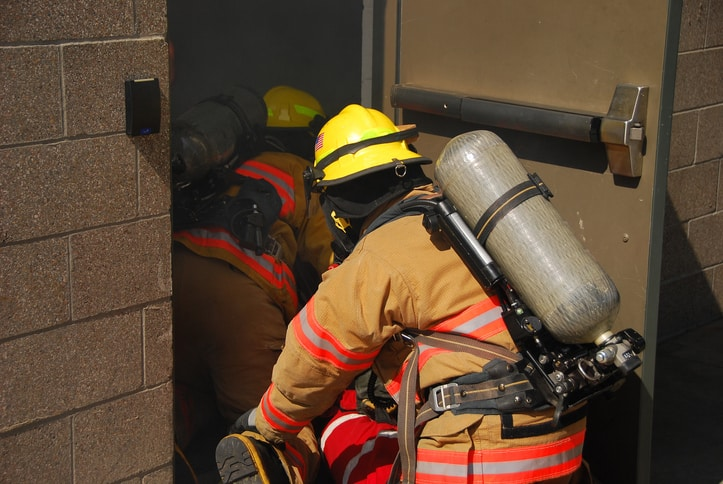 Two firefighters entering a building