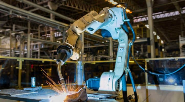 An industrial robot arm safely welds an automobile in an automated factory.
