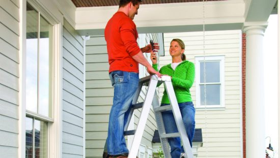 Couple in their new house practicing proper ladder safety.