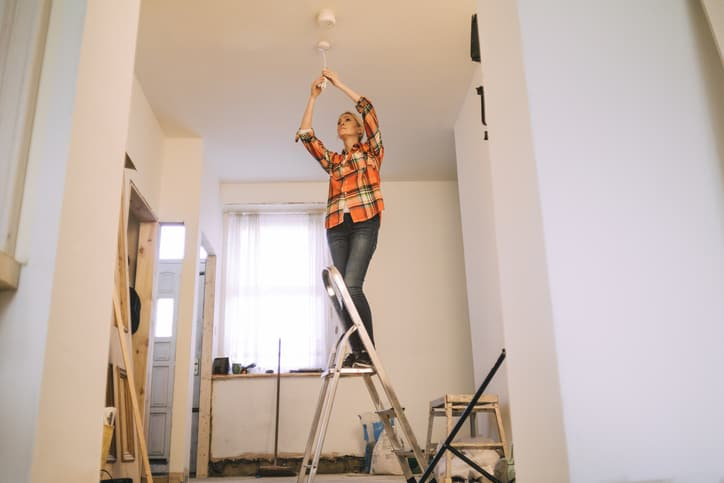 A woman safely operating a stepladder at home to change a lightbulb.