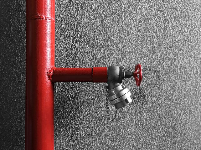 A red NFPA 14-2019 standpipe in front of wall