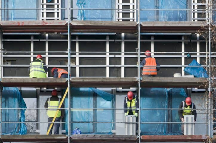Many construction workers being safe on ANSI/ASSP A10.8-2019 scaffolding