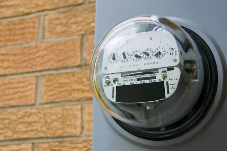 An electric meter on the side of a residential structure.