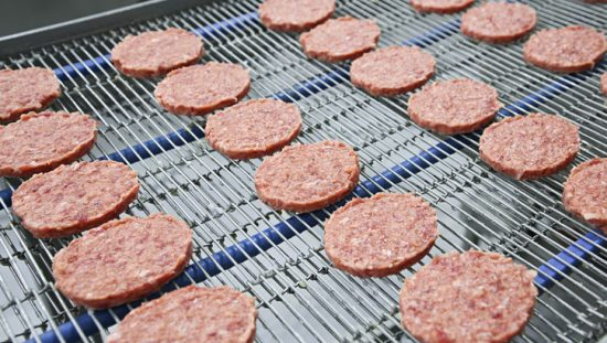 Burger patties sliding across NSF/ANSI/3A 14159-1-2019 meat processing equipment in a food plant.