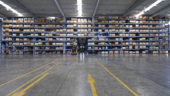 Guided industrial vehicle in warehouse using ANSI/ITSDF B56.5-2019 and automation to stack boxes