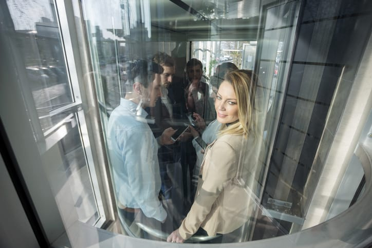 Happy people stuck in an elevator, which moves with ASME A15.5-2019.