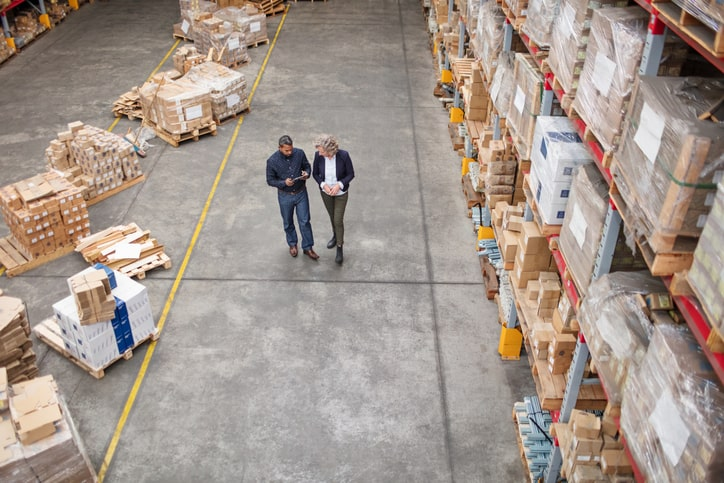 Two professionals in warehouse conducting an internal audit, not management review.