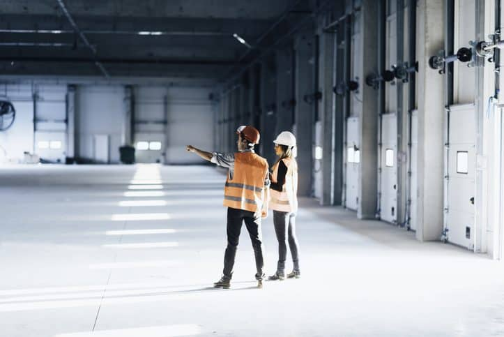 Safety professionals examining open facility in conducting ISO 41001 facility management.