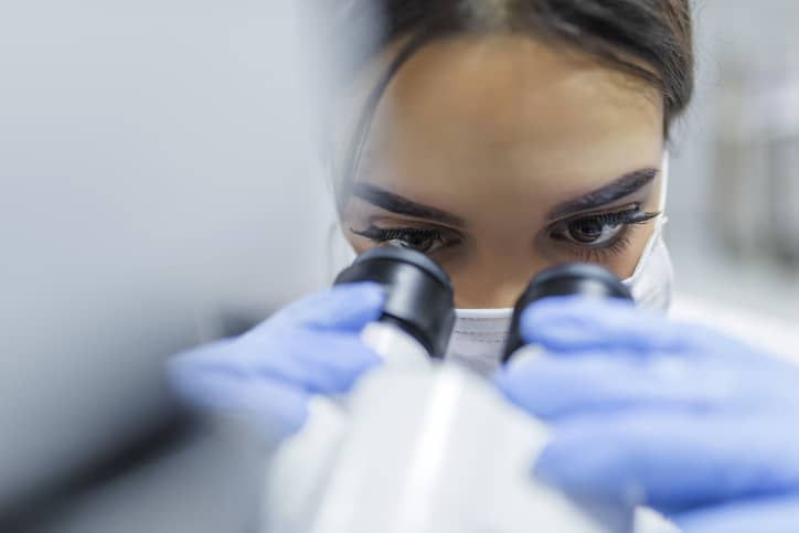 Scientist using root cause analysis via ISO/IEC 17025 to examine sample in microscope.
