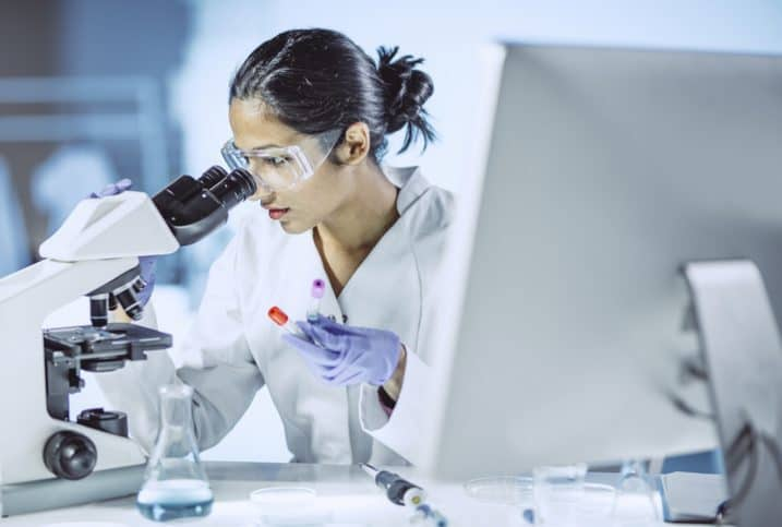 Woman examining microscopic sample and following updates to standards based on last ISO/IEC 17025 edition.