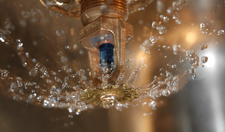 An indoor sprinkler with water coming out of it that is following NFPA 25-2020