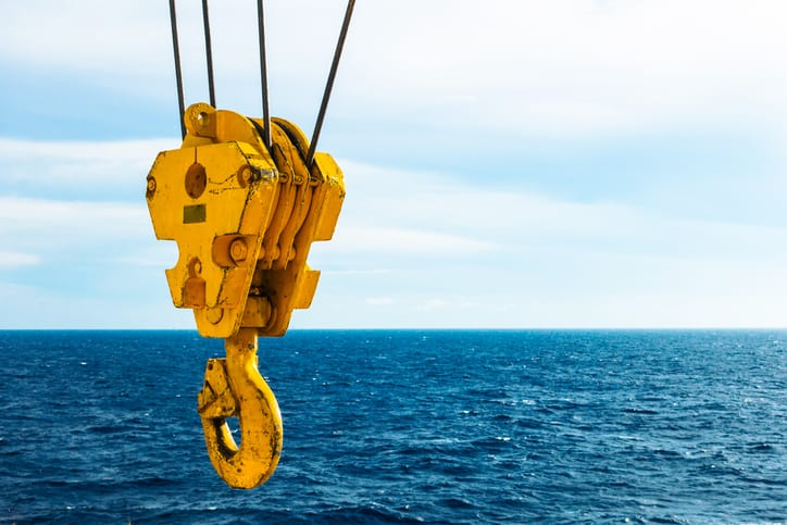Crane hook that follows the safety guidelines in ASME B30.10 with the ocean in the background