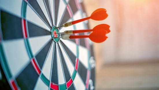 Three red darts find a bulls eye to depict accuracy and precision in ISO 5725-2:2019 that is repeatable.