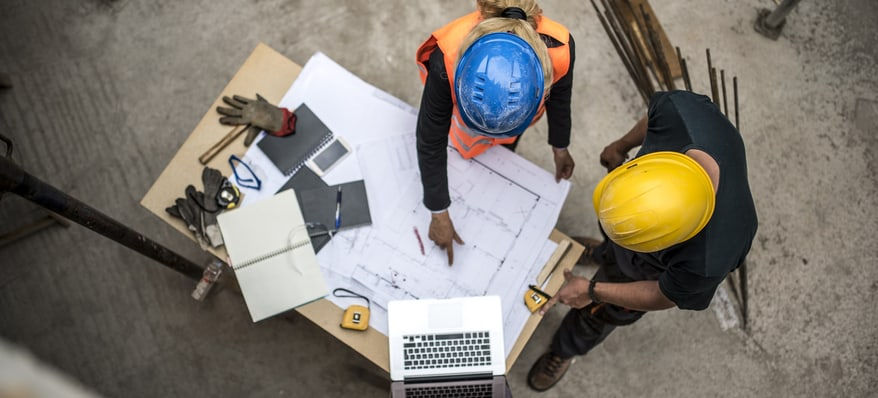 Overhead view of two construction workers discussing over a blueprint