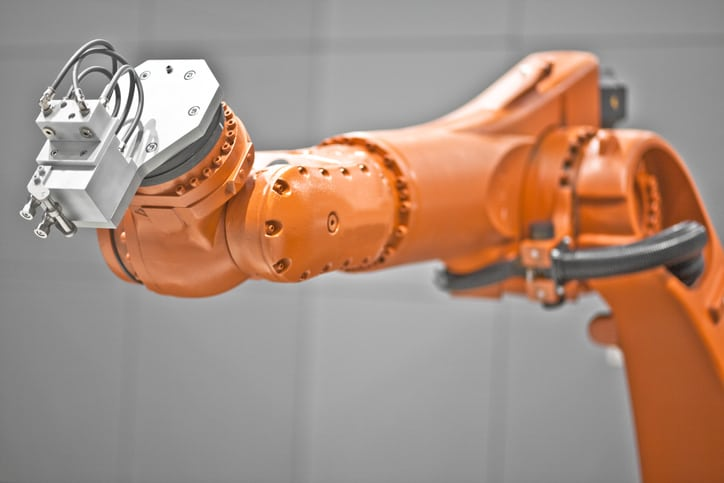 An orange ANSI B11.0-2020 robot arm not currently in operation.