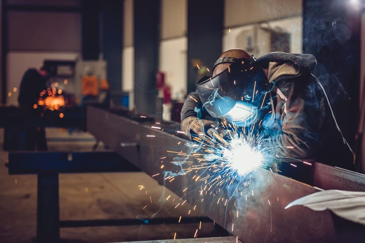 A person welding while following the guidelines set by AWS D1.1