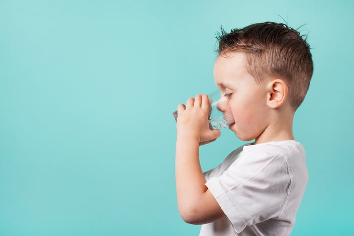 A boy hydrating with drinking water after being treated for NSF/ANSI 53-2020 health effect units.