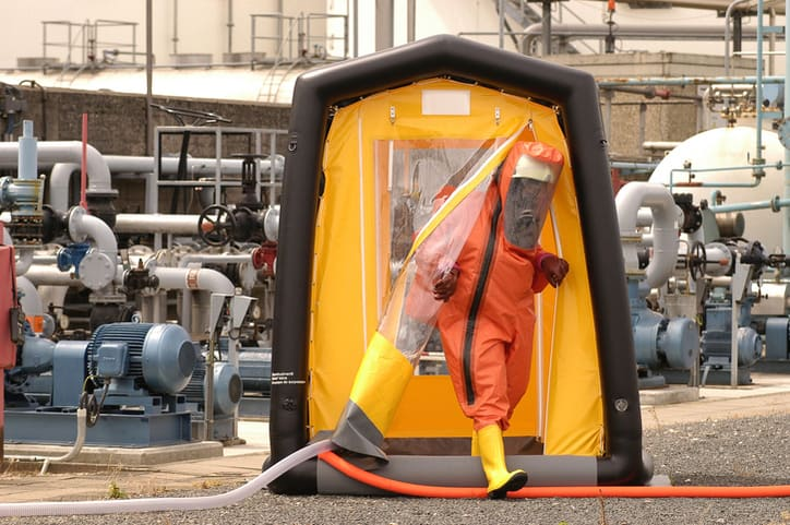 Doctor suited up stepping out of an ANSI/ISEA 113 decontamination shower.