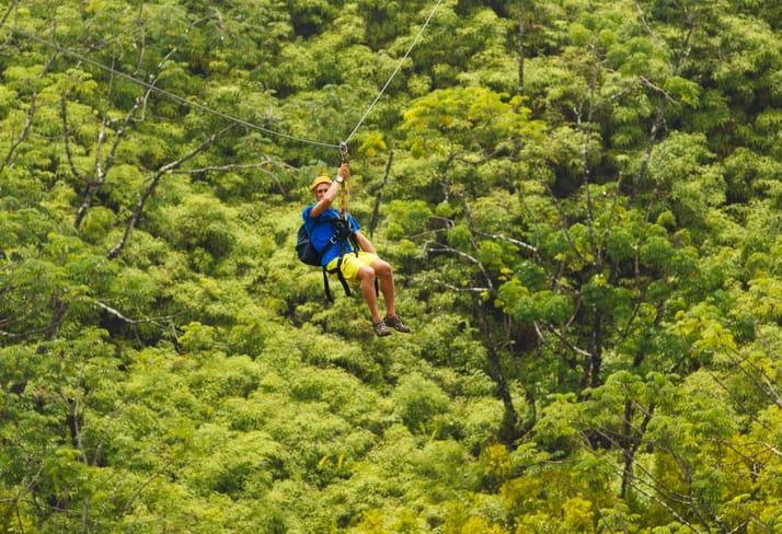 Adventure seeker sliding across ASTM F2959-21 zip line in the trees.